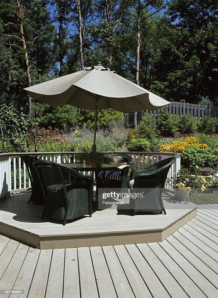 Dark Green Wicker Furniture Sits Around A Umbrella Table Stock Photo