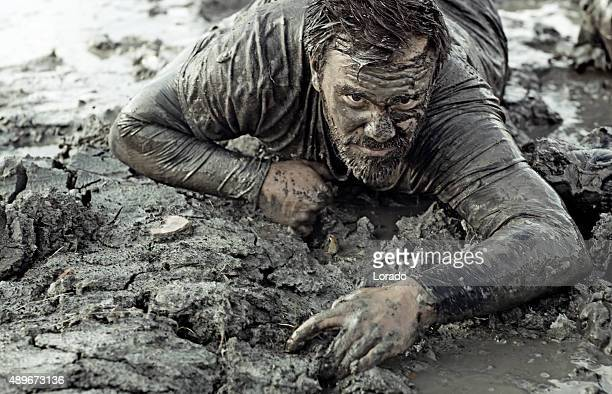 Dark haired man crawling during a mud run