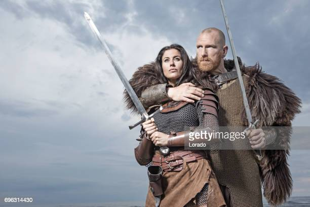 dark haired viking woman and bald viking man together in the sand - cosplay stock pictures, royalty-free photos & images