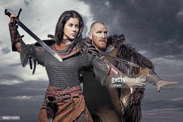 dark haired viking woman and bald viking man together in the sand - mulher guerreira imagens e fotografias de stock