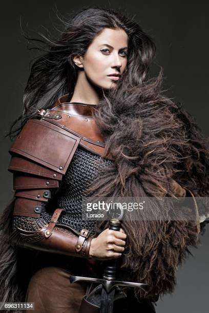 dark haired viking woman in studio setting - barbarian stock photos and pictures