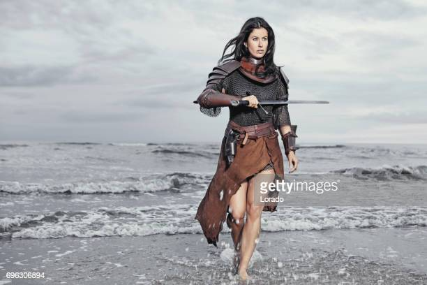 dark haired viking woman in the sea at dusk - barbarian stock photos and pictures
