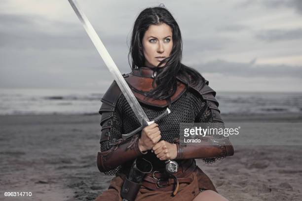 dark haired viking woman in the sea at dusk - mulher guerreira imagens e fotografias de stock