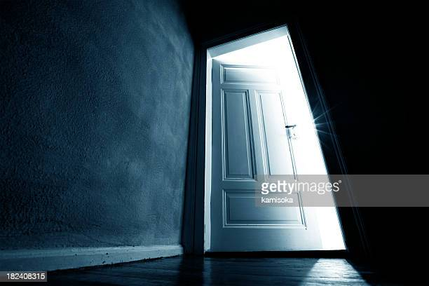 dark hallway with an opened door with bright light coming in - escapism stock photos and pictures
