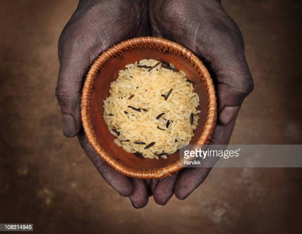 Dark Hands Holding Rice in Wooden Bowl