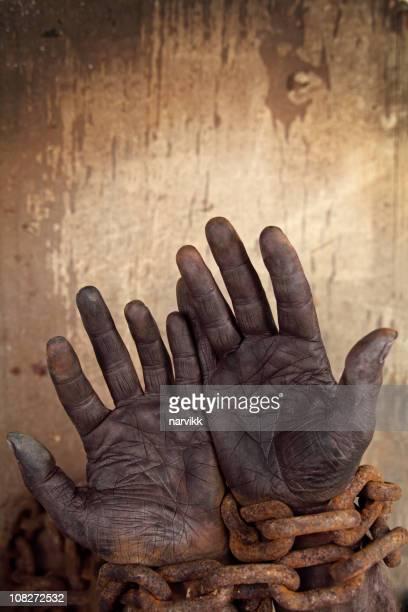 Dunkle Hände in starkem Ketten