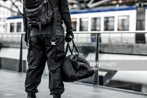 dark hooded terrorist figure at public transport hub - terrorism stock pictures, royalty-free photos & images