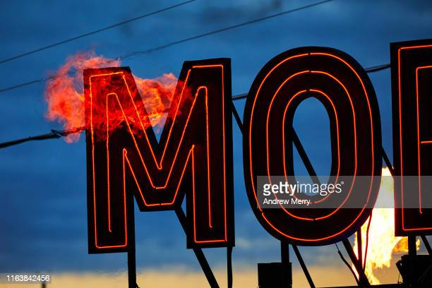 Dark MOFO neon sign glowing at night with fire