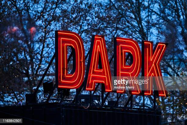 Dark MOFO neon sign glowing at night with trees