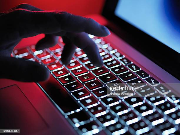 a dark mystery hand typing on a laptop computer at night - typen stockfoto's en -beelden
