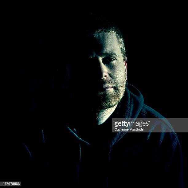 dark portrait of young man - catherine macbride stock pictures, royalty-free photos & images