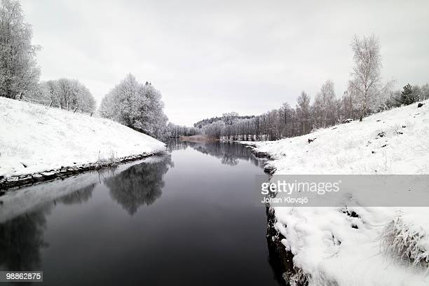 Dark river through snow-covered landscape