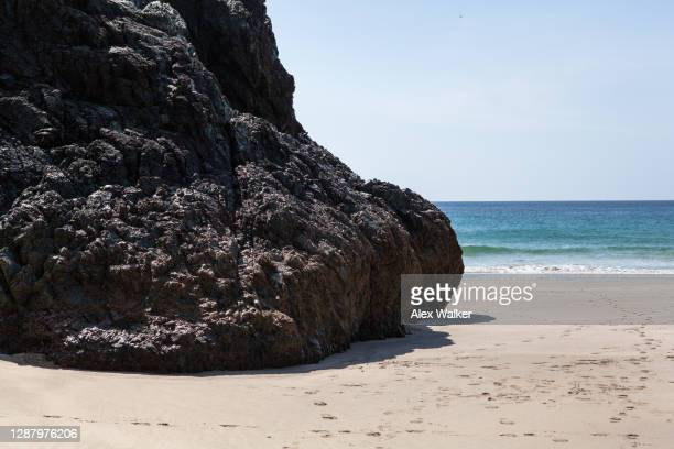 dark rocks on beach with blue water. - rock stock pictures, royalty-free photos & images