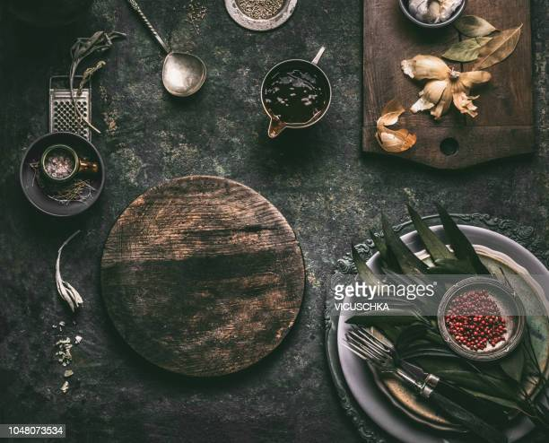 dark rustic food background with empty cutting board, sauce and table setting - kitchen background stock pictures, royalty-free photos & images