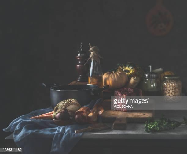 dark rustic kitchen table still life with black cooking pot, bottle of oil and fresh ingredients - stilleven stockfoto's en -beelden
