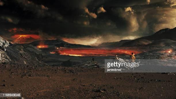 paisaje oscuro del planeta devastado. mujer mirando volcanes y meteoros - paisaje volcánico fotografías e imágenes de stock