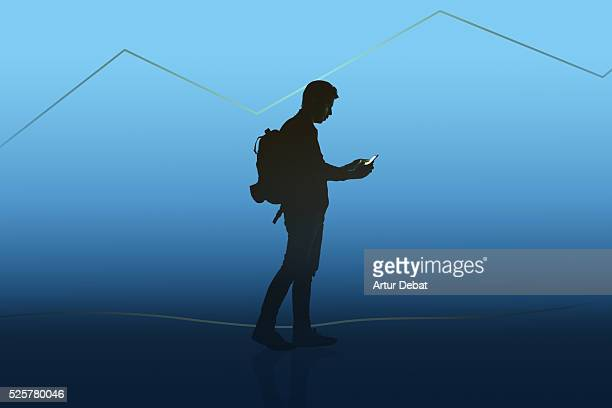 Dark silhouette of a guy isolated with a blue background holding a smartphone walking between the countryside with digital mountains only illuminated by the bright lights of the smartphone screen.
