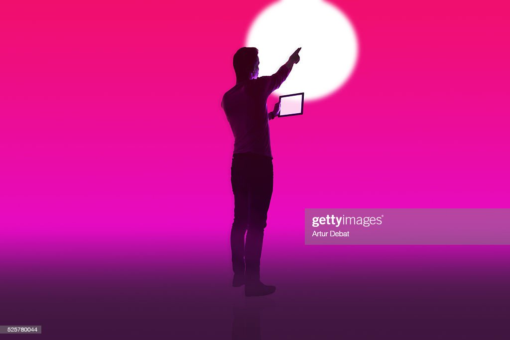Dark silhouette of a guy isolated with a colorful background dark silhouette of a guy isolated with a colorful background holding a tablet device interacting with voltagebd Choice Image
