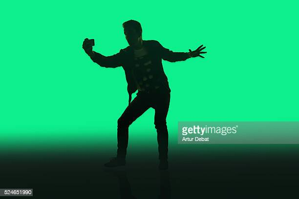Dark silhouette of a guy isolated with a green background holding and taking a selfie with smartphone only illuminated with the bright light of the smartphone screen.