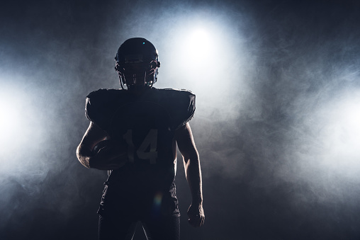 dark silhouette of equipped american football player with ball against white smoke 999876218