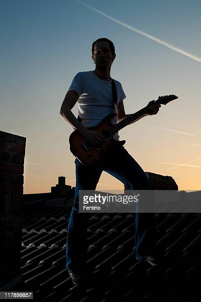 Dark Silhouette of Guitarist on a Roof at Sunset