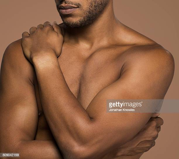 Dark skinned athletic male, close up on torso