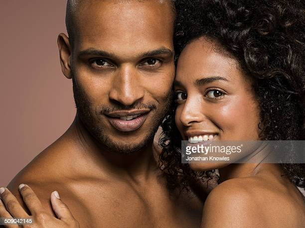 dark skinned couple holding each other, smiling - abrazo desnudos fotografías e imágenes de stock