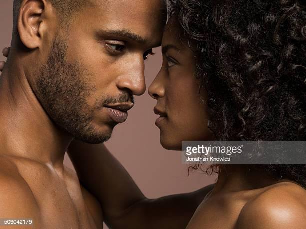 dark skinned couple looking into each others eyes - abrazo desnudos fotografías e imágenes de stock