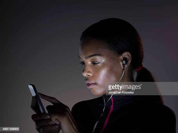 dark skinned female looking at her mobile phone - illuminated stock pictures, royalty-free photos & images