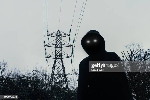 a dark spooky, moody edit. a hooded figure with glowing eyes, looking at the camera below an energy electricity pylon on a winters evening in the english countryside. - magic eye stock pictures, royalty-free photos & images