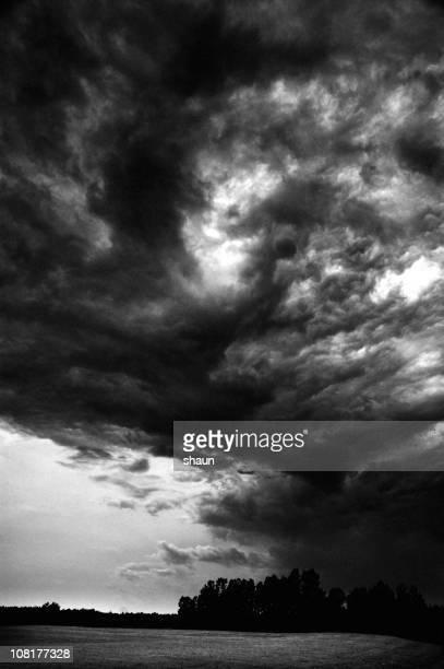 Nuvens de tempestade escuras acima campo, preto e branco