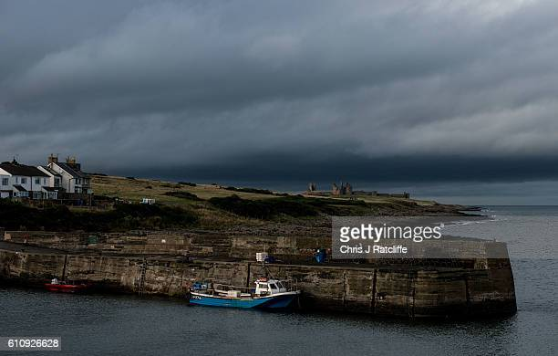 Dark storm clouds form over Dunstanburgh Castle on the coast of Northumberland as seen from the fishing port of Craster on September 28 2016 in...