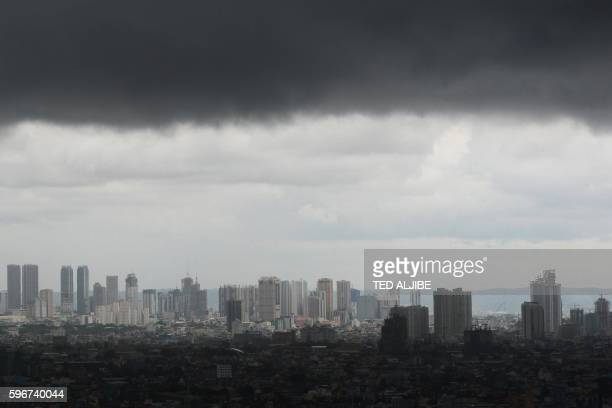 Dark stormclouds are seen over the Manila skyline on August 28, 2016. Cloudy skies with light to moderate rains and isolated thunderstorms are...