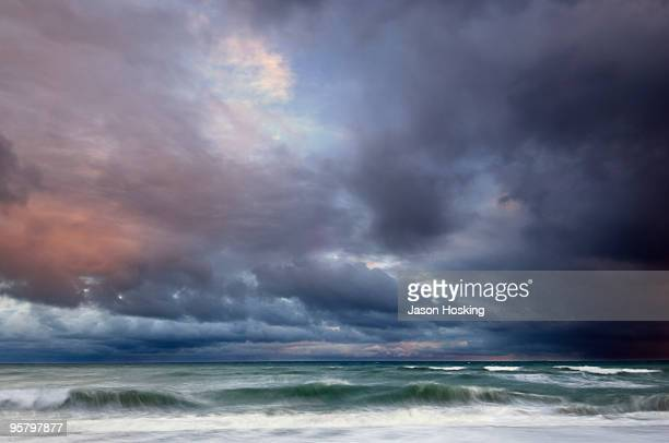 dark stormy sunset and clouds at sea - moody sky stock pictures, royalty-free photos & images