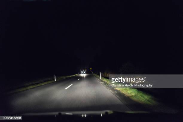 dark street at night with oncoming traffic - country road stock pictures, royalty-free photos & images