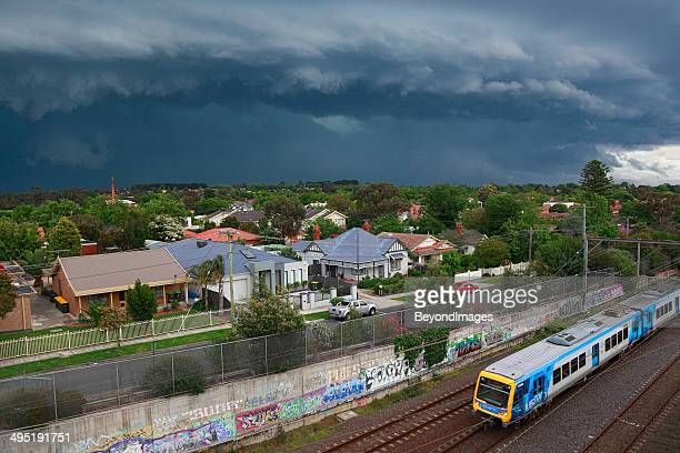 Dark, threatening storm looms over suburbs with metro train