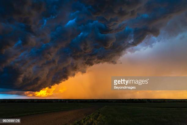 dark, turbulent, stormy sky at sunset in south dakota - nube temporalesca foto e immagini stock