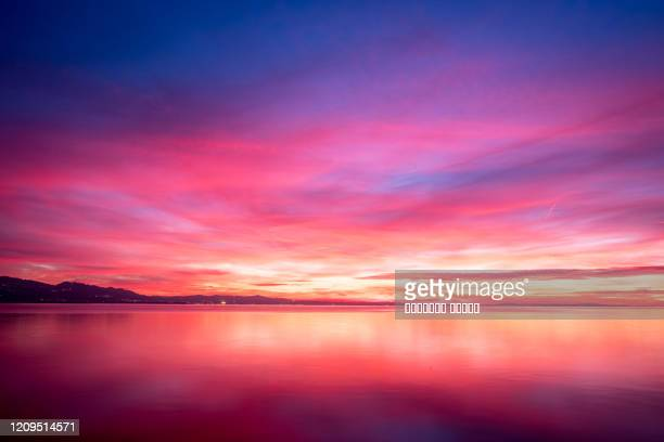 dark violet clouds with orange sun light and pink light in wonderful twilight sky on lake bodensee in lindau - paradise stock pictures, royalty-free photos & images