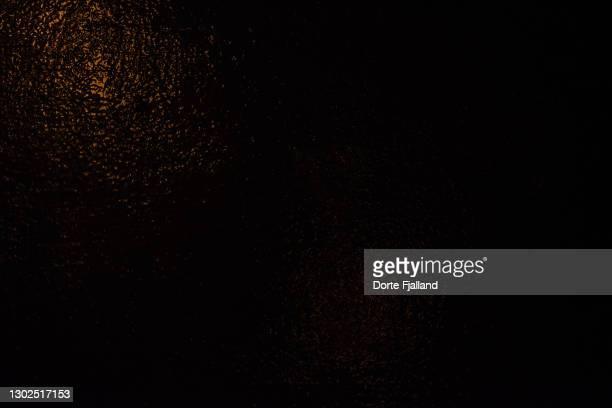 dark wall with a little golden light reflecting on it - dorte fjalland fotografías e imágenes de stock