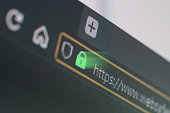 Dark web browser close-up on LCD screen with shallow focus on https padlock