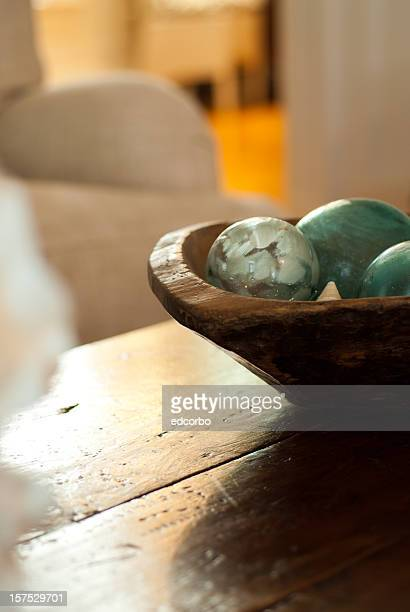 Dark wood coffee table with a bowl of green balls on