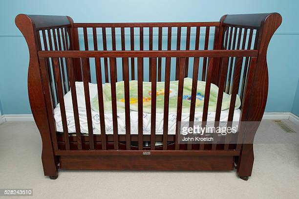 dark wood crib in a blue baby's room; millet, alberta, canada - empty crib stock photos and pictures