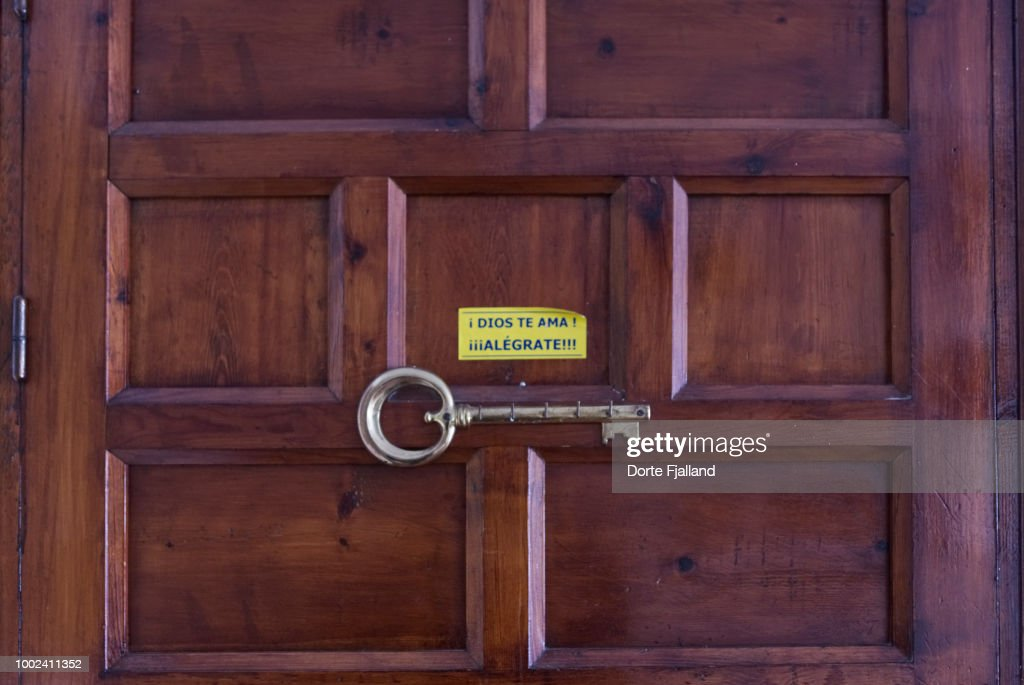 Dark wooden door with a key rack and a sticker with a message in Spanish: 'God loves you - Cheer up'' : Foto de stock