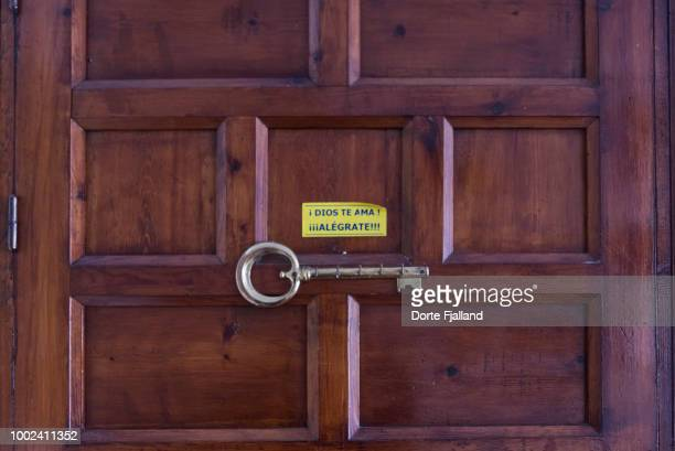 Dark wooden door with a key rack and a sticker with a message in Spanish: 'God loves you - Cheer up''