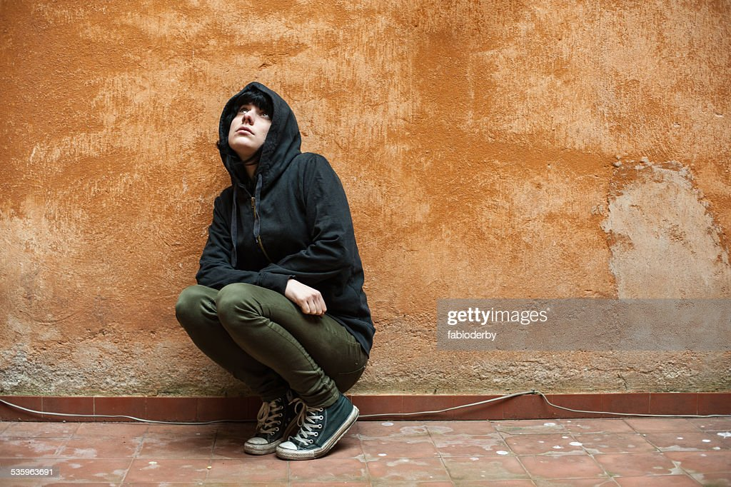 Dark young woman crouched near urban wall portrait : Stock Photo