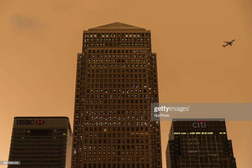Darkened sky over London is pictured at financial district of Canary Wharf, London on October 16, 2017. The darkening is caused by warm air and dust swept up by storm Ophelia. The sun shone red and the sky darkened to a foreboding orange and brown across parts of Britain.