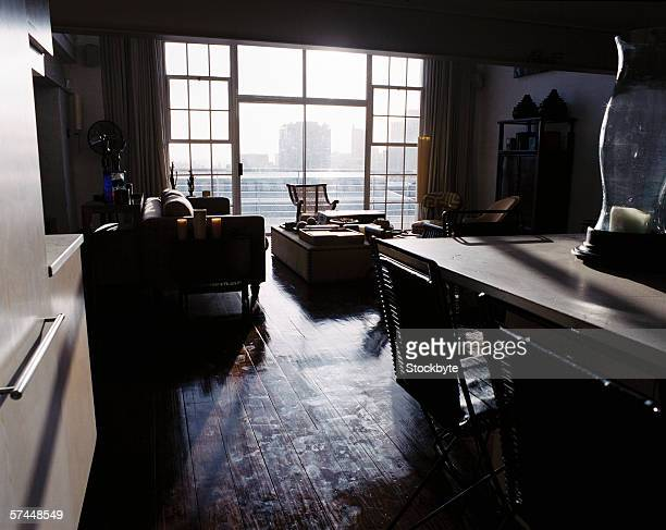 darkened view of a open kitchen overlooking the living room windows