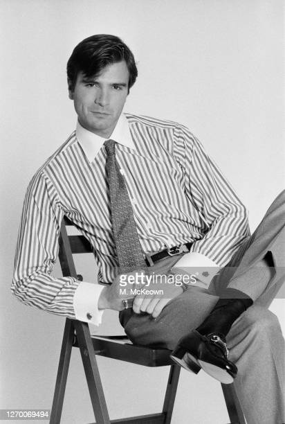 Dark-haired male model in a striped shirt with a white collar, and a tie, 17th January 1985.