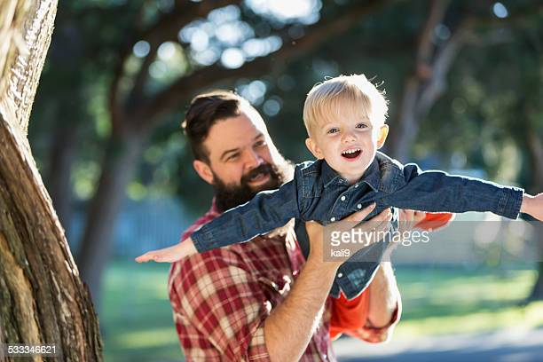 Dark-haired man with blond playful son