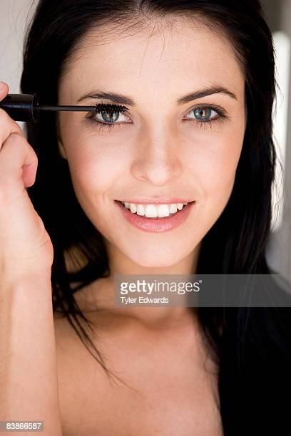 Dark-haired woman applying mascara